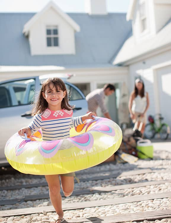 Child with inflatable swimming ring running outside vacation home in Orlando