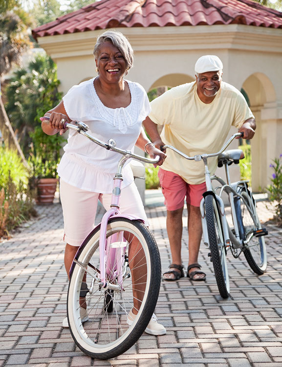 a man and woman riding a bike in 55 plus Community