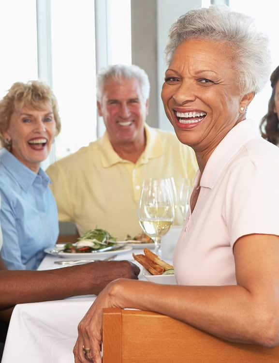 Retired woman enjoying lunch and glass of wine with friends