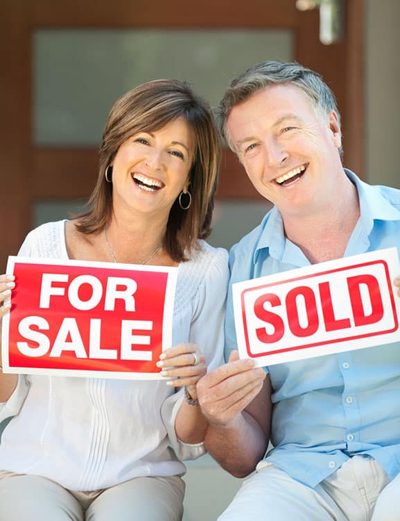 Retired couple smiling holding a for sale and sold sign