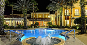 water fountain and pool lit up at night surrounded by palm trees